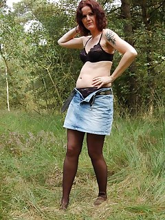 Naughty granny stripping down to her undies in a secluded park