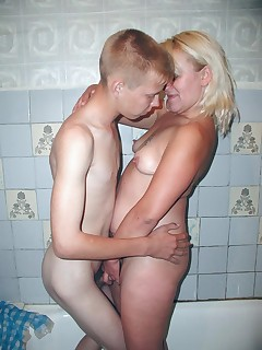 Blonde grandma playing with her young lover in the bath tub