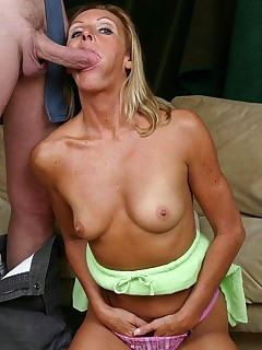 Blonde granny on her knees and deep throating a huge cock in the living room