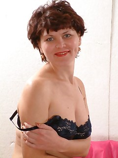 Brunette GILF acting sexy in front of the camera and playfully stripping off her clothes