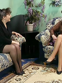 Two sexy mature babes sit on their couch and fill their mouths and pussies with dick