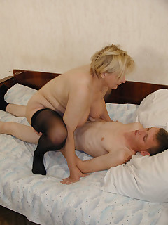Mature blonde rides young hard dick
