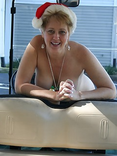 Tracy poses nude outdoors on a golf cart in a Santa hat